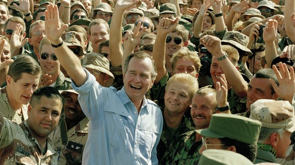 ARCHIV -- ZUM HEUTE VERSTORBENEN EHEMALIGEN US PRAESIDENT GEORGE BUSH,  STELLEN WIR IHNEN FOLGENDES BILDMATERIAL ZUR VERFUEGUNG -- FILE -- In this Nov. 22, 1990 file photo, President George Bush poses with soldiers during a stop at an air base in Dhahran, Saudi Arabia. Twenty five years after the first U.S. Marines swept across the border into Kuwait in the 1991 Gulf War, American forces find themselves battling the extremist Islamic State group, born out of al-Qaida, in the splintered territories of Iraq and Syria. Saddam Hussein, demonized as being worse than Adolf Hitler by President George H.W. Bush, would outlast his American rival in power until Bush's son launched the 2003 American-led invasion that toppled the Iraqi dictator. (AP Photo/J. Scott Applewhite, File)