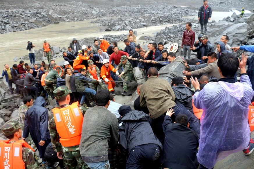 epa06048770 Rescuers work at the site of a massive landslide where over 120 villagers are estimated to be buried, in Maoxian county, southwest China's Sichuan province, 24 June 2017. Six bodies have been found so far. The landslide was triggered after a mountain side collapsed on 23 June, due to heavy rains.  EPA/STRINGER CHINA OUT