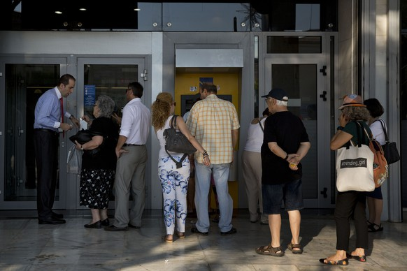 """An elderly woman asks a question to a bank employee as people line up to an ATM machine outside the bank in Athens, on Monday, July 6, 2015. Greece's Finance Minister Yanis Varoufakis has resigned following Sunday's referendum in which the majority of voters said """"no"""" to more austerity measures in exchange for another financial bailout. (AP Photo/Petros Giannakouris)"""