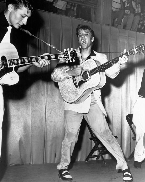 TAMPA, FL - JULY 31: Rock and roll singer Elvis Presley performs on stage with his brand new Martin D-28 acoustic guitar and Scotty Moore on the left on July 31, 1955 at Fort Homer Hesterly Armory in Tampa, Florida. (Photo by Michael Ochs Archives/Getty Images)