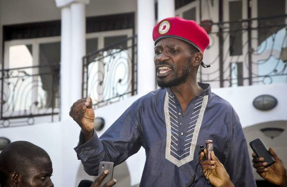FILE - In this Thursday, May 2, 2019 file photo, Ugandan pop star singer and political opposition activist Bobi Wine, whose real name is Kyagulanyi Ssentamu, greets his followers as he arrives home after being released from prison on bail in Kampala, Uganda. Protests have broken out in Uganda's capital, Kampala, after police arrested Bobi Wine who is seeking the presidency in next year's election, with Wine's supporters blocking roads and burning tires, prompting police to fire tear gas and rubber bullets to disperse the protesters. (AP Photo/Ronald Kabuubi, File) Bobi Wine,Kyagulanyi Ssentamu