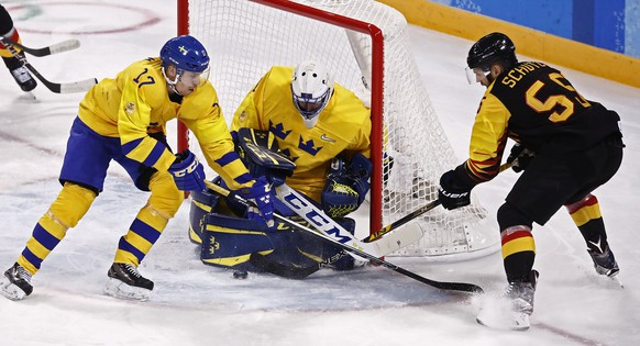 epa06532568 Goalie Jhonas Enroth (C) and Par Lindholm (L) of Sweden blocks a shot against Felix Schutz (R) of Germany during their preliminary round match inside the Kwandong Hockey Centre at the PyeongChang Winter Olympic Games 2018, in Gangneung, South Korea, 16 February 2018. The PyeongChang 2018 Winter Olympic Games, will run from 09 to 25 February 2018.  EPA/LARRY W. SMITH