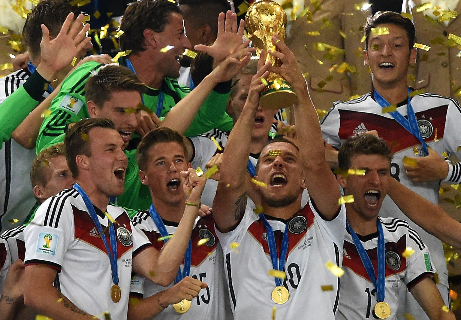Germany's forward Lukas Podolski (front R) and team-mates celebrate with the World Cup trophy after they won the 2014 FIFA World Cup final football match between Germany and Argentina 1-0 following extra-time at the Maracana Stadium in Rio de Janeiro, Brazil, on July 13, 2014.         AFP PHOTO / PEDRO UGARTE