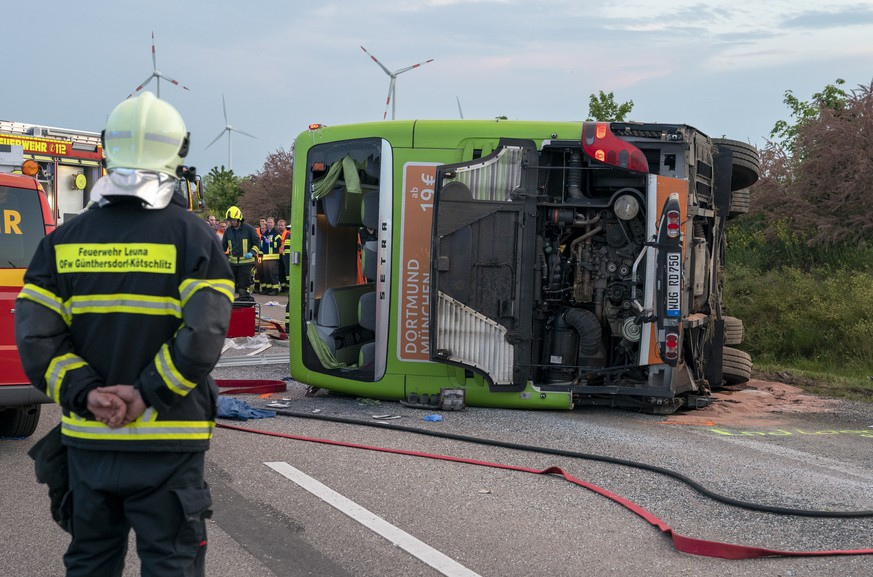 epa07585394 A fireman looks at the wreckage of a bus of Flixbus at the motorway parking place 'Bachfurt West' near Leipzig, Germany, 19 May 2019. The bus overturned for no apparent reason. According to the local police, one person was killed in the accident, and others seriously injured.  EPA/ALEXANDER BECHER