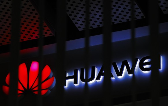 FILE - In this March 8, 2019, file photo, A logo of Huawei retail shop is seen through a handrail inside a commercial office building in Beijing.  The U.S. government is imposing new restrictions on Chinese tech giant Huawei by limiting its ability to use American technology to build its semiconductors. The Commerce Department said Friday, May 15, 2020 the move aims to cut off Huawei