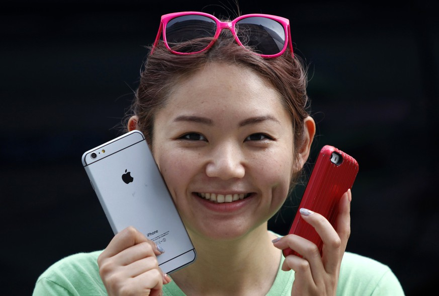 A woman holds a mock iPhone 6 plus (L) and an iPhone 5s as she waits in a line, ahead of the September 19 release of iPhone 6 and iPhone 6 Plus, in front of an Apple Store at Tokyo's Ginza shopping district September 10, 2014. Apple Inc unveiled a watch, two larger iPhones and a mobile payments service on Tuesday as Chief Executive Officer Tim Cook seeks to revive the technology company's reputation as a wellspring of innovation. REUTERS/Yuya Shino (JAPAN - Tags: BUSINESS SOCIETY SCIENCE TECHNOLOGY TELECOMS)