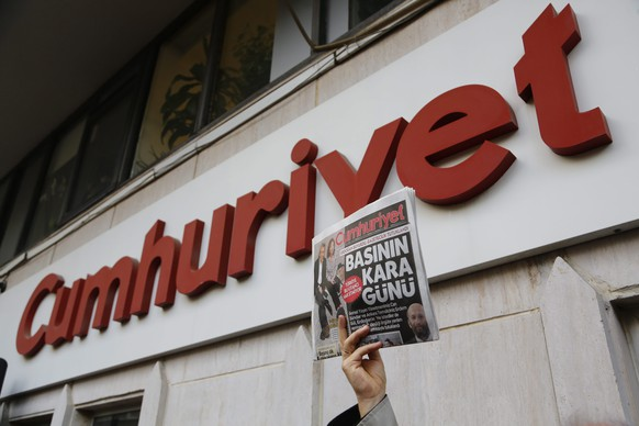 epa05044744 A Turkish man holds the Cumhuriyet newspaper as others gather in protest  in front Turkish newspaper Cumhuriyet publishing house, in support of Can Dundar and Erdem Gul who were arrested by an Istanbul court in Istanbul, Turkey, 27 November 2015. The editor in chief of Turkish newspaper Cumhuriyet and its Ankara correspondent were arrested on 26 November after publishing a report about the delivery of weapons from Turkey to extremists in Syria. Editor Can Dundar and journalist Erdem Gul of the Cumhuriyet newspaper, which is critical of the government of President Recep Tayyip Erdogan, face charges of belong to a terrorist group and espionage.  EPA/CEM TURKEL