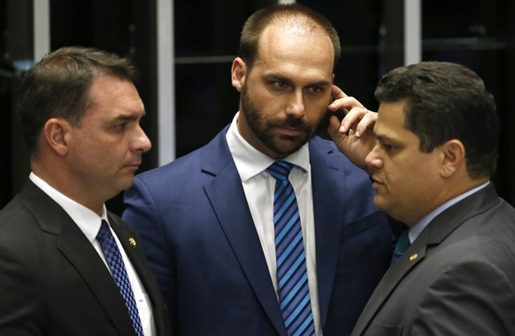 Senate President Davi Alcolumbre, right, talks with lawmaker Eduardo Bolsonaro, center, and Senator Flavio Bolsonaro, the son of the nation's president, during the final voting session on pension reform at the Senate in Brasilia, Brazil, Tuesday, Oct. 22, 2019. The most meaningful impact is the establishment of a minimum age for retirement at 65 for men and 62 for women. (AP Photo/Eraldo Peres) Davi Alcolumbre,Eduardo Bolsonaro,Flavio Bolsonaro
