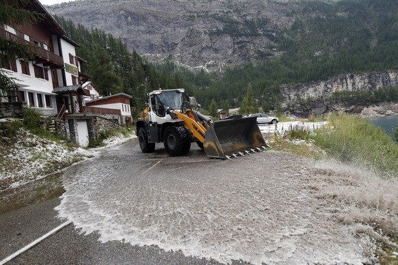 A worker uses a snow shovel to clean the road of the nineteenth stage of the Tour de France cycling race over 126,5 kilometers (78,60 miles) with start in Saint Jean De Maurienne and finish in Tignes, France, Friday, July 26, 2019. Tour de France organizers stopped Stage 19 of the race because of a hail storm as Julien Alaphilippe lost his yellow jersey to Egan Bernal. (AP Photo/Thibault Camus)