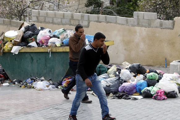 epa04631991 Palestinian men hold their noses to protect themselves from the smell of garbage piled up in the Old City in the West Bank city of Hebron, 22 February 2015.  EPA/ABED AL HASLHAMOUN