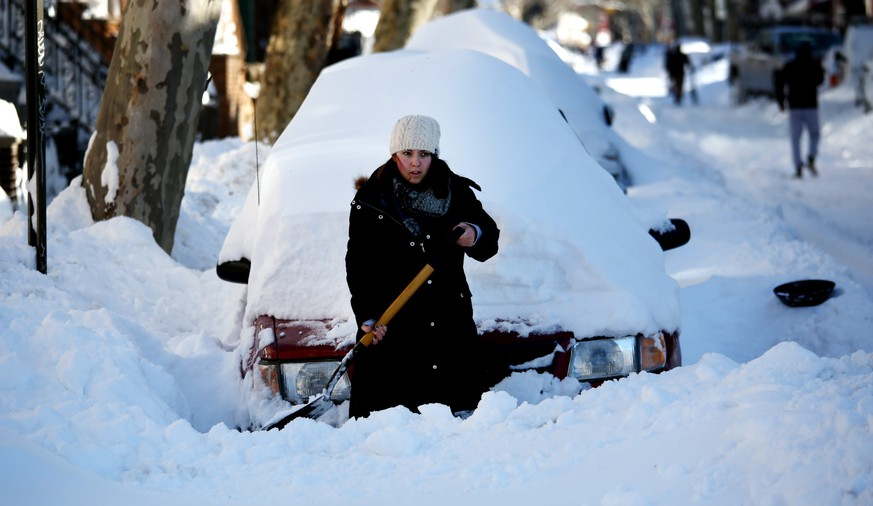 epa05123402 A woman works on digging out her car  following a snow storm in Brooklyn, New York, USA, 24 January 2016. The storm dumped large amounts of snow on the east coast of the United States.  EPA/JUSTIN LANE