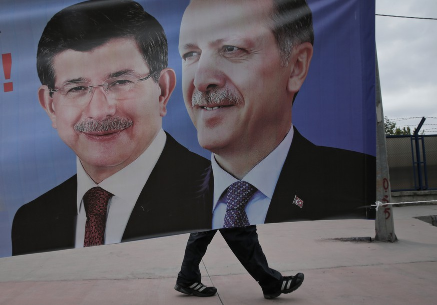 FILE - In this Thursday, May 28, 2015 file photo, a man walks past a poster with pictures of Turkish Prime Minister and leader of the ruling Justice and Development Party _ known by its Turkish acronym, AKP, left, and Turkey's President Recep Tayyip Erdogan and party's former leader, right, in Istanbul, Turkey. Following the June 7, 2015 elections, experts agree on one thing: No one really knows what's going to happen next. Turkey's election left Turkey's long-ruling Justice and Development Party _ known by its Turkish acronym, AKP _ short of the majority it needs to govern alone, meaning it will have to turn to one (or more) of the three opposition parties to secure its hold on government. (AP Photo/Lefteris Pitarakis, File)