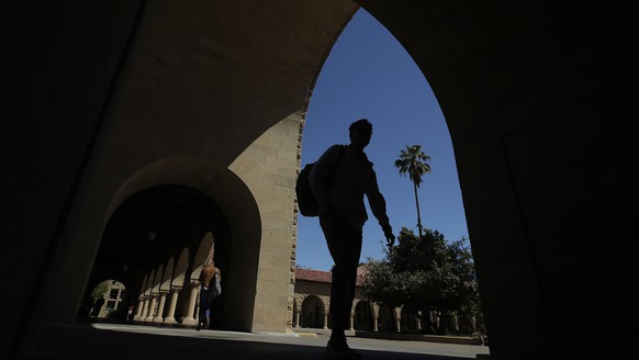 FILE - In this April 9, 2019, file photo, pedestrians walk on the campus at Stanford University in Stanford, Calif. College students who earned money this summer can make the most of it by including a few longer-term financial goals in their budgeting. (AP Photo/Jeff Chiu, File)
