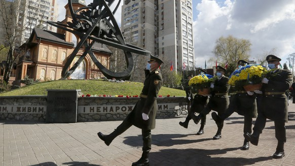 Guards of Honor march to lay a flower wreath at Chernobyl's victim monument in Ukraine's capital Kyiv, Ukraine, Monday, April 26, 2021. April 26 marks the 35th anniversary of the Chernobyl nuclear disaster. A reactor at the Chernobyl nuclear power plant exploded on April 26, 1986, leading to an explosion and the subsequent fire spewed a radioactive plume over much of northern Europe. (AP Photo/Efrem Lukatsky).