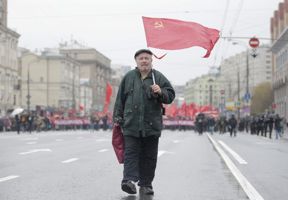 epa04728323 A man carries a Russian Communist party flag as members and supporters move to the center of Moscow during a traditional May Day demonstration, Russia, 01 May 2015. Some 140,000 workers and students attended the parade on the occasion of Labour Day, also known as International Worker's Day or May Day.  EPA/MAXIM SHIPENKOV