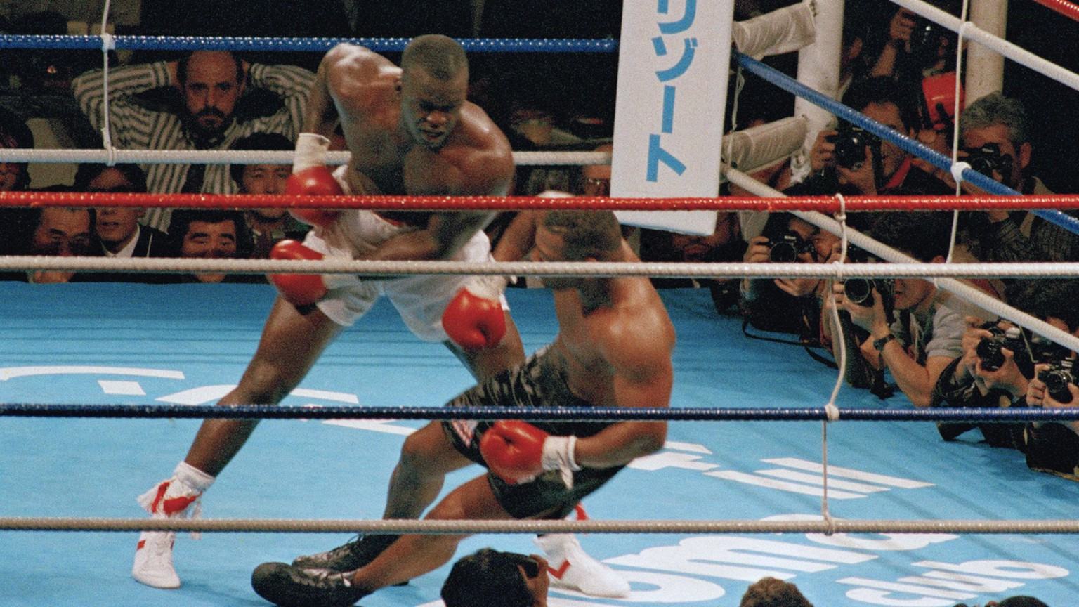FILE - In this Feb. 11, 1990, file photo, James Douglas follows with a left, dropping Mike Tyson to the canvas in the 10th round of scheduled 12-round heavyweight champion bout at the Tokyo Dome in Tokyo. Tyson, the youngest heavyweight champion in boxing history, comes into the bout 37-0 with 33 knockouts, while the unknown Douglas is 29-4-1 with 19 KOs. (AP Photo/Tsugufumi Matsumoto, File)