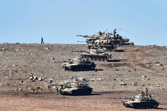 TOPSHOTS Turkish tanks line up on a hill outside the village of Mursitpinar next to the Syrian town of Ain al-Arab, known as Kobane by the Kurds, on the Turkish-Syrian border in the southeastern town of Suruc, Sanliurfa province, on October 6, 2014. Turkish security forces on Monday used tear gas to push dozens of reporters and Kurdish civilians away from the border zone close to intense fighting for the besieged Syrian town of Kobane. AFP PHOTO / ARIS MESSINIS