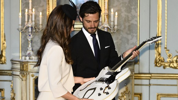 epa04753033 Sweden's Prince Carl Philip (R) and his fiancee Sofia Hellqvist look at a guitar that was given to them as a gift during a reception at the Royal Palace in Stockholm, Sweden, 17 May 2015, after a service in the Royal Chapel where the banns of marriage for Prince Carl Philip and Sofia Hellqvist was read during Sunday's service. Their wedding is scheduled for 13 June.  EPA/CLAUDIO BRESCIANI / TT SWEDEN OUT