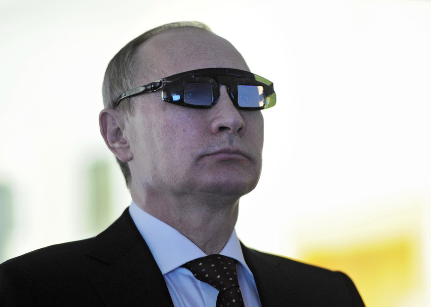 Russian President Vladimir Putin wears special glasses as he visits a recearch facility in