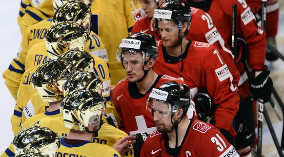 epa03708304 Swedish players, (L) shake hands with Swiss players after Sweden won the 2013 Ice Hockey IIHF World Championships final match between Switzerland and Sweden at the Ericsson Globe Arena in Stockholm, Sweden, 19 May 2013.  EPA/CLAUDIO BRESCIANI SWEDEN OUT