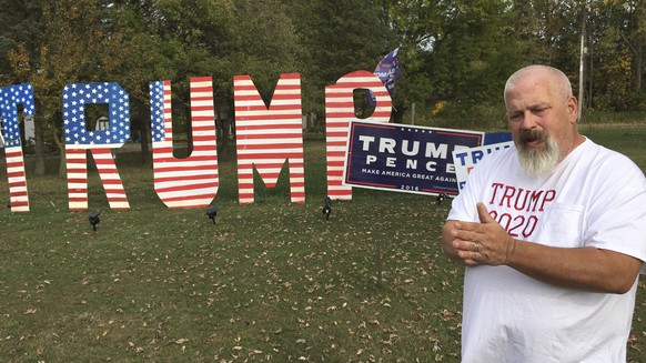 Mike Devore poses near an 8-foot tall sign he made in his yard to show his support for President Donald Trump in Wayne, Ohio on Wednesday, Oct. 14, 2020. Devore lives in Wood County, an election bellwether that only once since 1964 has not picked the presidential winner. Ohio is again up for grabs in the presidential election. But only a handful of the state's counties have reliably gotten the outcome right going back over many decades. (AP Photo/John Seewer)