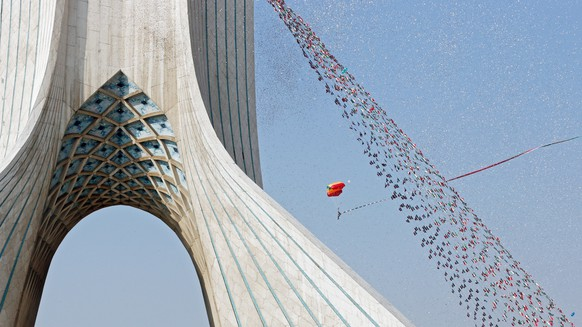 epa06514408 An Iranian parachuter descends with Iran's national flag during a ceremony marking the 39th anniversary of the 1979 Islamic revolution around the Azadi (Freedom) square in Tehran, Iran, 11 February 2018. The event marks the 39th anniversary of the Islamic revolution, which came ten days after Ayatollah Ruhollah Khomeini's return from his exile in Paris to Iran, toppling the monarchy system and forming the Islamic republic.  EPA/ABEDIN TAHERKENAREH