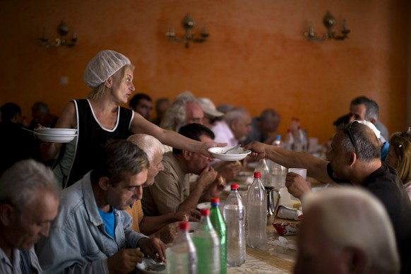 """Needy people eat at the Church-run Galini charity's soup kitchen in central Athens on Monday, July 6, 2015. Greece's finance minister has resigned following Sunday's referendum in which the majority of voters said """"no"""" to more austerity measures in exchange for another financial bailout. (AP Photo/Emilio Morenatti)"""
