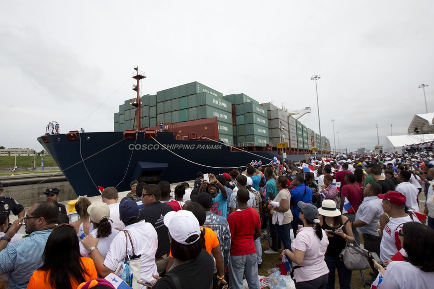 Spectators watch as the Neopanamax cargo ship, Cosco Shipping Panama, begins to cross the new Agua Clara locks, part of the Panama Canal expansion project, near the port city of Colon, Panama, Sunday June 26, 2016. The ship carrying more than 9,000 containers entered the newly expanded locks that will double the Panama Canal's capacity in a multibillion-dollar bet on a bright economic future despite tough times for international shipping. (AP Photo/Moises Castillo)