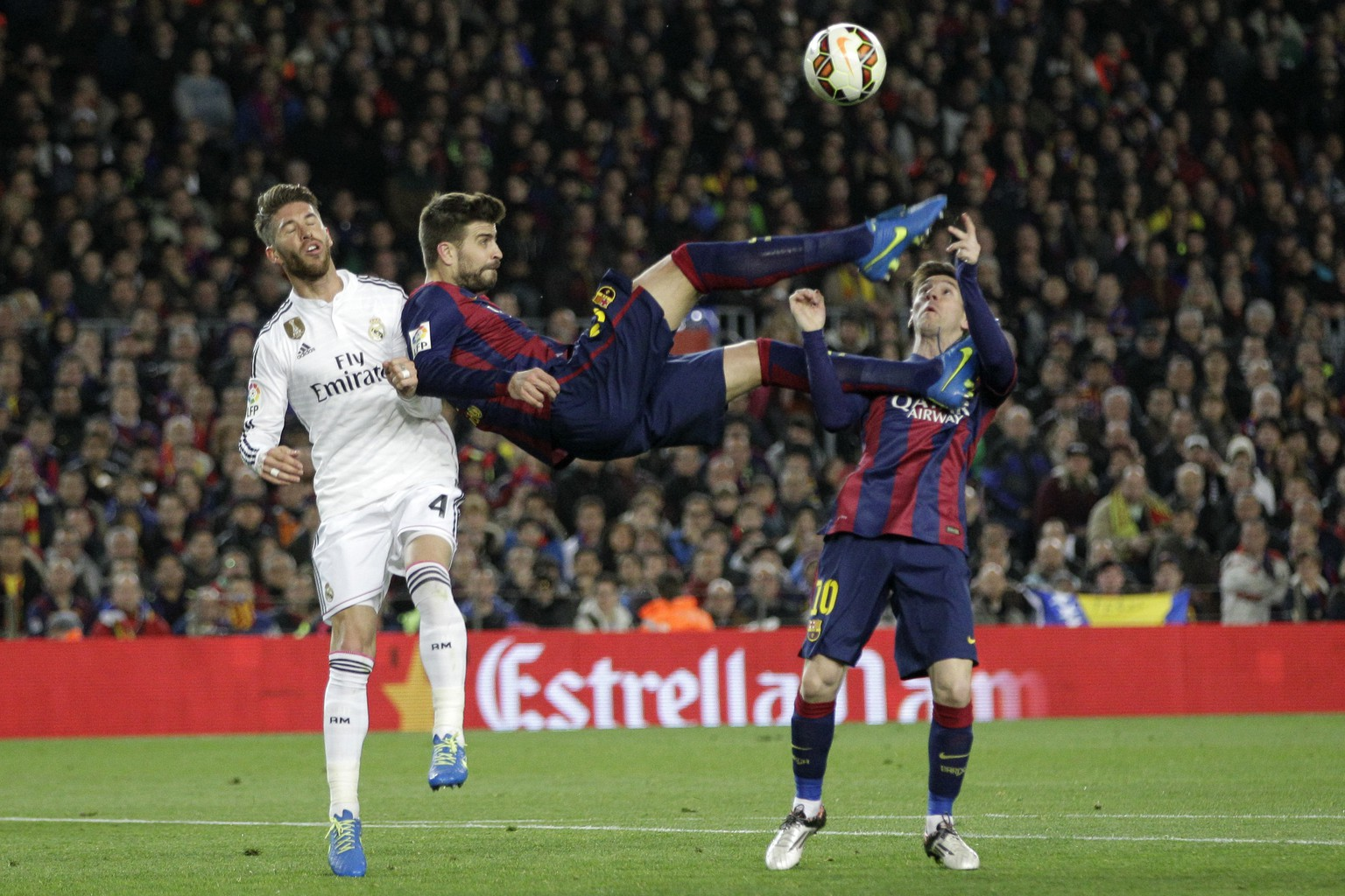 FILE- In this Sunday, March 22, 2015 file photo, Barcelona's Gerard Pique kicks the ball with Real Madrid's Sergio Ramos, left, and Barcelona's Lionel Messi, right, during a Spanish La Liga soccer match between FC Barcelona and Real Madrid at Camp Nou stadium, in Barcelona, Spain. A spat between Barcelona's Gerard Pique and Real Madrid's Sergio Ramos has added fuel to a heated title race. (AP Photo/Emilio Morenatti, File)