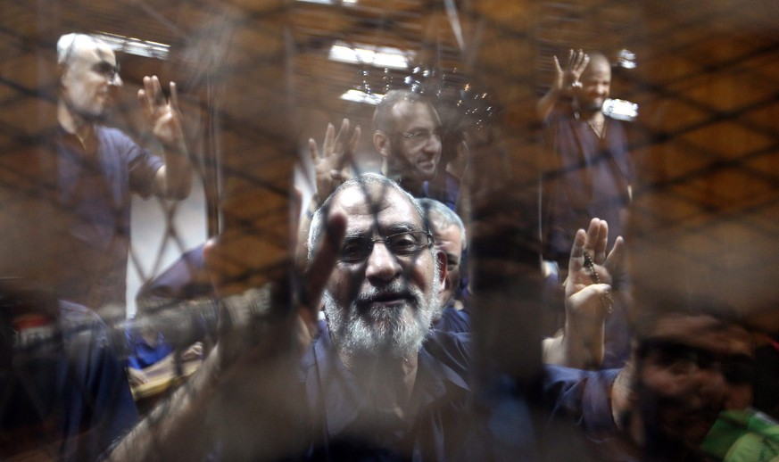 epa04665239 (FILE) A file picture dated 13 July 2014 shows Egypt's Muslim Brotherhood Supreme Guide Mohamed Badie (C) flashing the four-finger sign from behind dock bars during a trial session, in Cairo, Egypt. According to media reports on 16 March 2015, Badie, along with 13 other members of the Muslim Brotherhood, has been given a death sentence.  EPA/KHALED ELFIQI