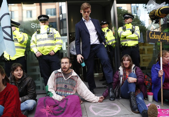 A man walks out of the Home office past climate change protesters on the second day of ongoing protests in London, Tuesday, Oct. 8, 2019. Police are reporting they have arrested more than 300 people at the start of two weeks of protests as the Extinction Rebellion group attempts to draw attention to global warming. (AP Photo/Alastair Grant)