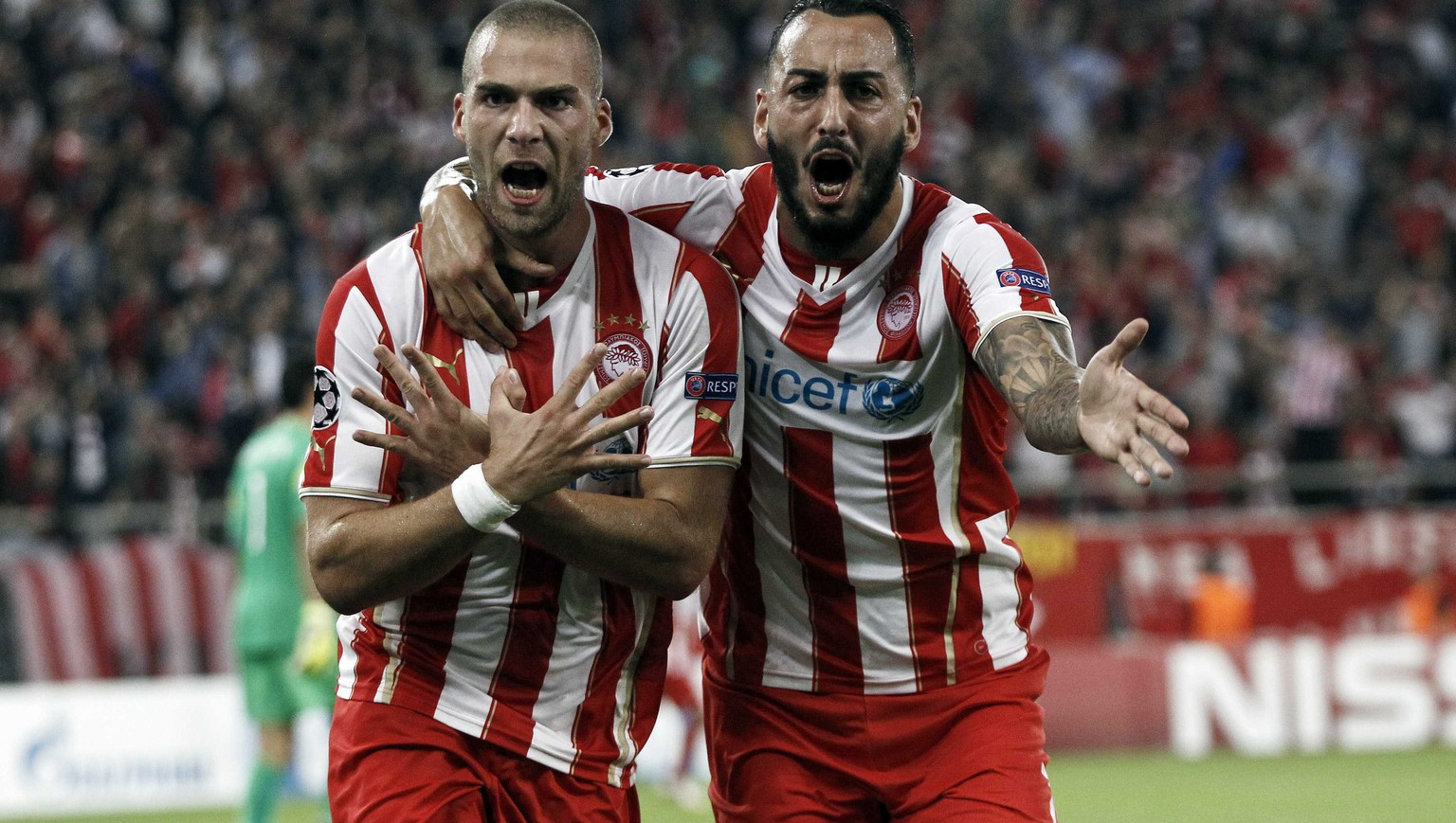 Olympiakos' Pajtim Kasami (L) celebrates his goal with teammate Kostas Mitroglou during their Champions League soccer match against Juventus at Karaiskaki stadium at Karaiskaki stadium in Piraeus, near Athens, October 22, 2014.  REUTERS/Alkis Konstantinidis  (GREECE - Tags: SPORT SOCCER)