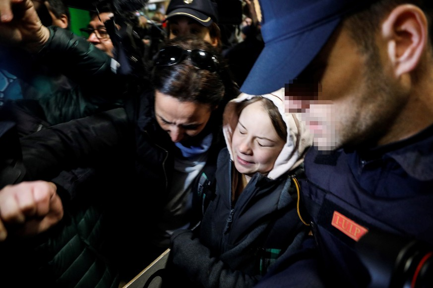 epa08048257 Swedish environmental activist Greta Thunberg (C) is surrounded by journalists upon her arrival at Chamartin Railway Station, in Madrid, Spain, early 06 December 2019. Greta arrived in Madrid after a ten-hour journey by train from Lisbon, Portugal to attend the Global March for Climate rally that will be held in the Spanish capital this evening -- on the sidelines of the UN Climate Change Conference COP25, which runs from 02 to 13 December 2019.  EPA/DAVID FERNANDEZ -- ATTENTION EDITORS: FACE OF OFFICERS PIXELATED AT SOURCE IN ACCORDANCE WITH SPANISH LAW