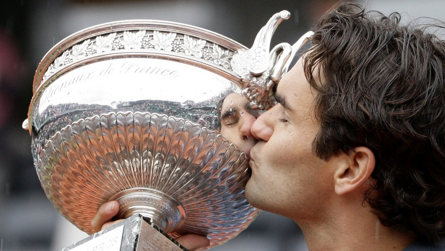 Switzerland's Roger Federer kisses the trophy after defeating Sweden's Robin Soderling during their men's singles final match of the French Open tennis tournament at the Roland Garros stadium in Paris, Sunday June 7, 2009. The victory gives Federer 14 Grand Slams, tying his career wins to American Pete Sampras. (AP Photo/Bernat Armangue)