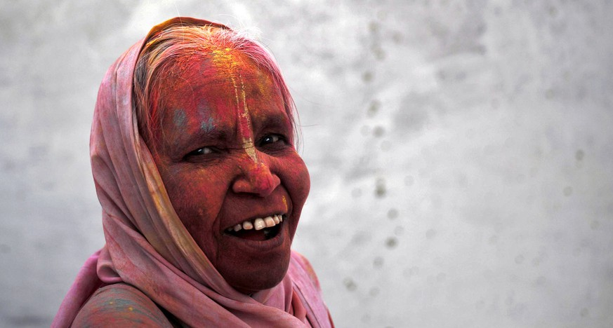 A widow daubed in colours takes part in the Holi celebrations organised by non-governmental organisation Sulabh International at a ashram at Vrindavan, in the northern state of Uttar Pradesh, India, March 22, 2016. Traditionally in Hindu culture, widows are expected to renounce earthly pleasure so they do not celebrate Holi. But women at the shelter for widows, who have been abandoned by their families, celebrated the festival by throwing flowers and coloured powder. Holi, also known as the Festival of Colours, heralds the beginning of spring and is celebrated all over India. REUTERS/Anindito Mukherjee      TPX IMAGES OF THE DAY
