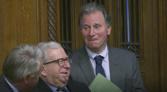 Oliver Letwin, right, listens as Prime Minister Boris Johnson delivers a statement to lawmakers inside a crowded House of Commons in London, Saturday Oct. 19, 2019. At a rare weekend sitting of Parliament, Johnson implored legislators to ratify the Brexit deal he struck this week with the other 27 EU leaders. Lawmakers are to be granted a chance to vote Saturday on the Oliver Letwin amendment to the Brexit deal, which may delay their final decision on Brexit. (House of Commons via AP)