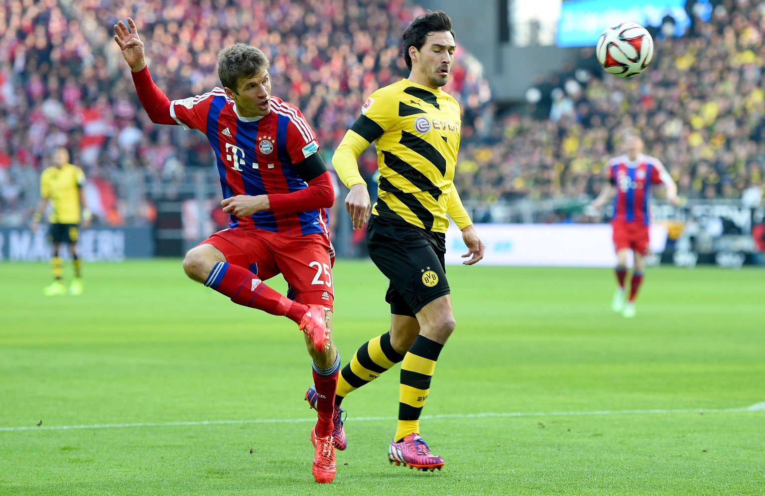 DORTMUND, GERMANY - APRIL 04: Thomas Mueller of Bayern Muenchen shoots on goal next to Mats Hummels of Borussia Dortmund during the Bundesliga match between Borussia Dortmund and FC Bayern Muenchen at Signal Iduna Park on April 4, 2015 in Dortmund, Germany.  (Photo by Lars Baron/Bongarts/Getty Images)