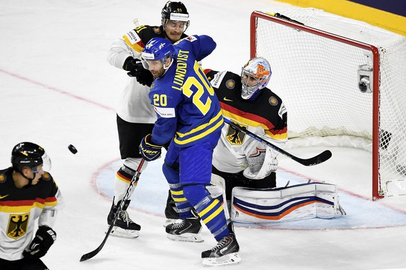 epa05947285 Sweden's forward Joel Lundqvist (C) in action against Germany's goalie Thomas Greiss (R) and Moritz Mueller (2-L) during the 2017 IIHF Ice Hockey World Championship group A preliminary round match between Germany and Sweden in Cologne, Germany, 06 May 2017.  EPA/SASCHA STEINBACH