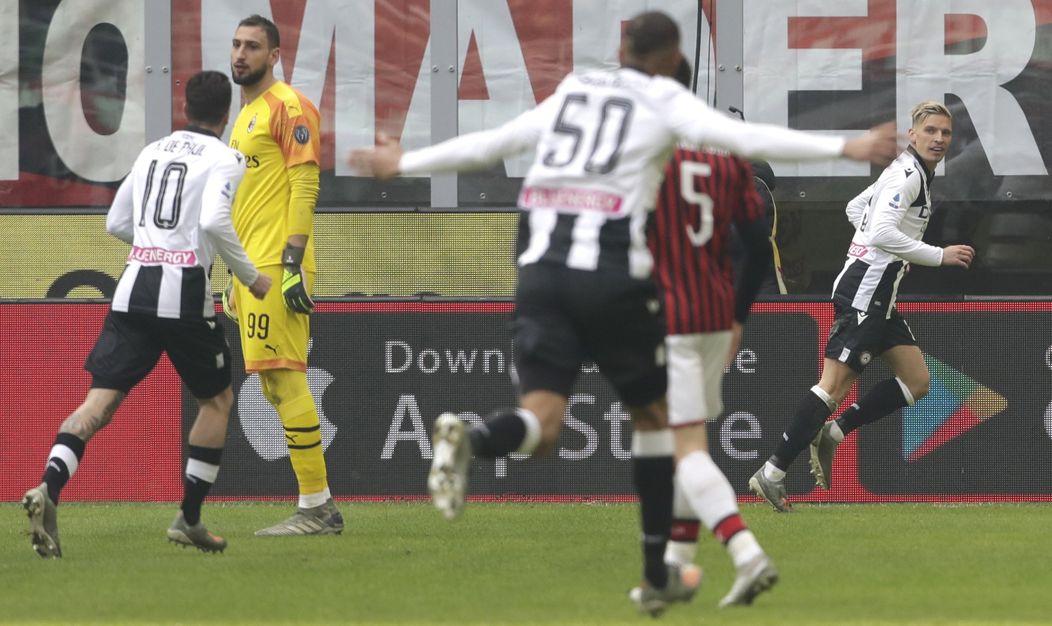Udinese's Jens Stryger Larsen celebrates after scoring his side's opening goal during a Serie A soccer match between AC Milan and Udinese, at the San Siro stadium in Milan, Italy, Sunday, Jan. 19, 2020. At left is AC Milan's goalkeeper Gianluigi Donnarumma.(AP Photo/Luca Bruno)