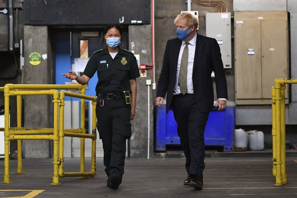 Britain's Prime Minister Boris Johnson, wearing a face mask, talks with paramedic Cindy Fu during a visit to the headquarters of the London Ambulance Service NHS Trust in London, Monday July 13, 2020. (Ben Stansall/Pool via AP)