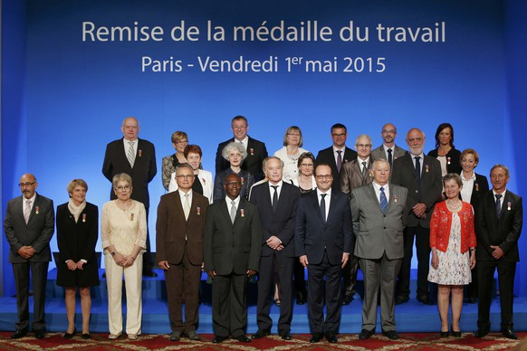 French President Francois Hollande (4thR) and Minister of Labour Francois Rebsamen (5thR) pose with people who received Working Medal of Honor awards at a ceremony on May Day at the Elysee Palace, in Paris, France, May 1, 2015.  REUTERS/Yoann Valat/Pool