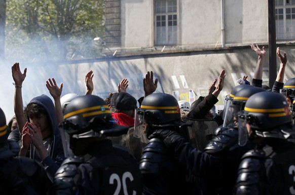 Youths raise their hands high to show that they do not hold bottles or stones as they pass French riot police during a protest against the French labour law proposal during the May Day labour union march in Paris, France, May 1, 2016.    REUTERS/Philippe Wojazer
