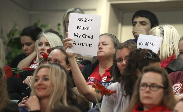 A sign expressing opposition to SB277, a measure that will require California schoolchildren to get vaccinated, is displayed as lawmakers discuss the bill at the Capitol in Sacramento, Calif. Wednesday, April 22, 2015. The bill by Sens. Ben Allen, D-Santa Monica, and Richard Pan, D-Sacramento, was approved by the Senate Education Committee on a 7-2 vote after the authors made amendments that allows families who chose to not vaccinate to homeschool children together and allows independent study. The bill now goes to the Senate Judiciary Committee.(AP Photo/Rich Pedroncelli)