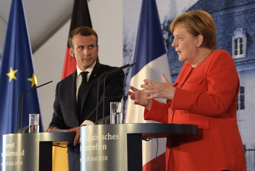 France's President Emmanuel Macron, left, listens to German Chancellor Angela Merkel at a press conference after a meeting in the guest house of the German government in Meseberg north of Berlin, Germany, Tuesday, June 19, 2018. (AP Photo/Jens Meyer)