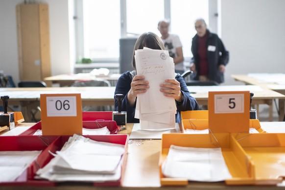 Eine Wahlhelferin in Zürich sortiert Wahlzettel.