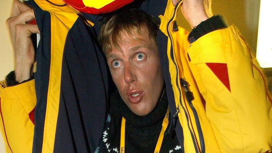 Cross country skier Johann Muehlegg takes cover from photographers as he arrives for a television interview in Salt Lake City February 24, 2002. The IOC announced that Muehlegg had been found guilty of doping and would be barred from the Winter Olympics. (KEYSTONE/EPA PHOTO/DPA/Stephan Jansen)