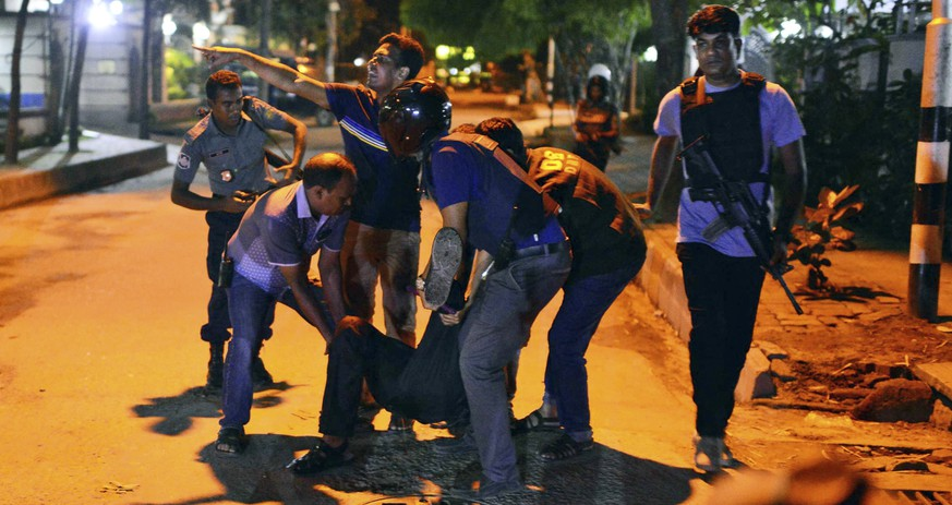 People help an unidentified injured person after a group of gunmen attacked a restaurant popular with foreigners in a diplomatic zone of the Bangladeshi capital Dhaka, Bangladesh, Friday, July 1, 2016. A group of gunmen attacked a restaurant popular with foreigners in a diplomatic zone of the Bangladeshi capital on Friday night, taking hostages and exchanging gunfire with security forces, according to a restaurant staff member and local media reports. (AP Photo)