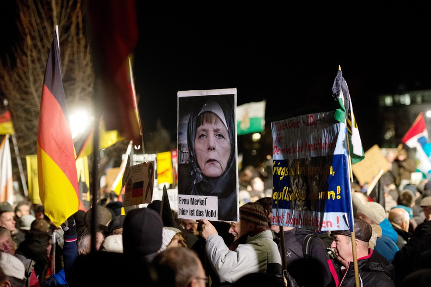 epa04557360 Participants in a rally with the Anti-Islamic Pegida (Patriotic Europeans against the Islamization of the West) movement hold up a picture of Chancellor Merkel wearing a headscarf written with the words 'Mrs. Merkel - here is the people' and flags in Dresden, Germany, 12 January 2015. Pediga has called again for a demonstration in the Saxon capital. Islam is part of German life, Chancellor Angela Merkel said 12 January 2015, even as a group of anti-Islam and anti-refugee protesters geared up for controversial marches that have become a weekly fixture in the eastern city of Dresden.  EPA/ARNO BURGI