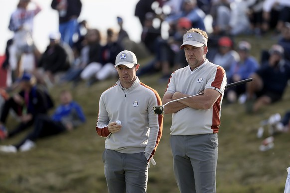 epa09488682 European team member Ian Poulter of England (R) and Rory McIlroy of Northern Ireland (L) look on from the 11th green during the Four-Ball matches on the pandemic-delayed 2020 Ryder Cup golf tournament at the Whistling Straits golf course in Kohler, Wisconsin, USA, 25 September 2021. Competition for the 43rd Ryder Cup between the US and Europe begins 24 September 2021.  EPA/TANNEN MAURY