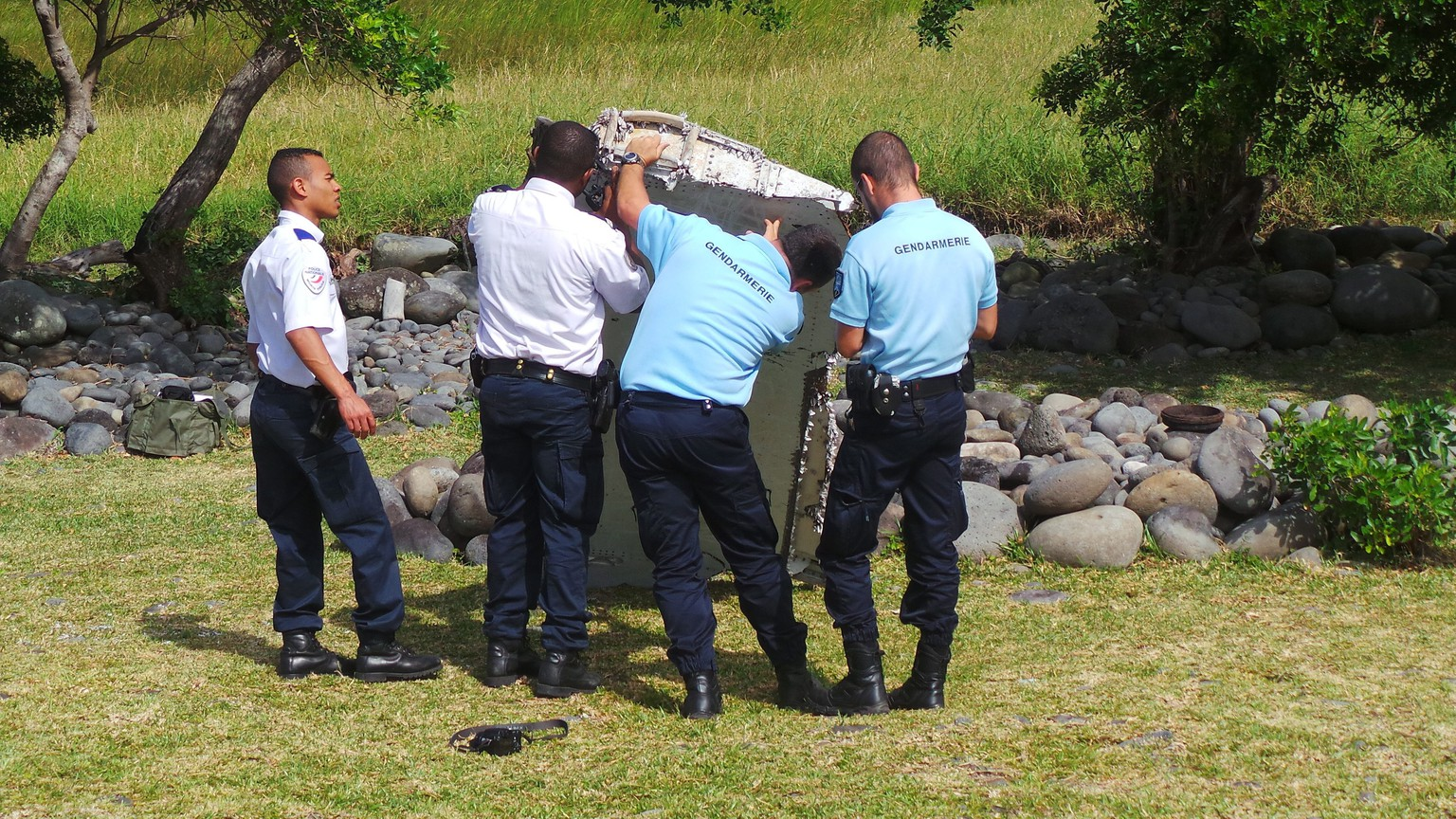 epa04866272 A picture made available 30 July 2015 shows members of French Gendarmerie and local authorities checking a piece of debris from an unidentified aircraft apparently washed ashore in Saint-Andre de la Reunion, eastern La Reunion island, France, 29 July 2015. A Malaysian government team is being dispatched to the French island of Reunion in the Indian Ocean, where newly found aircraft wreckage awakened speculation over flight MH370, which went missing last year with 239 people aboard.  EPA/ZINFOS974